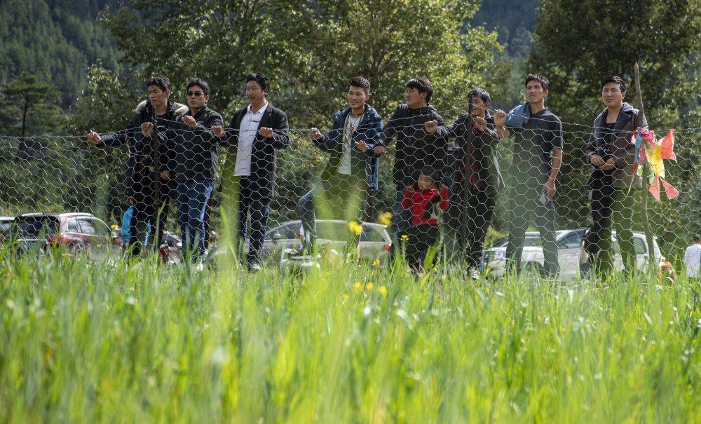 西藏林芝市米林县里龙乡德吉新村村民围在人工草场周围查看饲草长势(9月13日摄)。新华社记者 孙非 摄