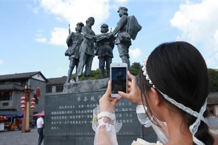 游客朱志群在村里游玩,不忘用手机记录行程