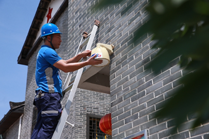 中国电信装维工程师钟常勇在检修村里的摄像头