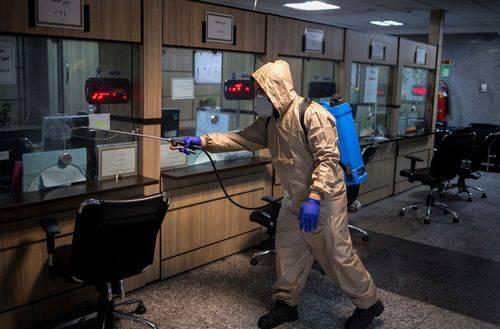 3月7日,在伊朗德黑兰的伊朗卫生部,一名工作人员在进行消毒。新华社发(艾哈迈德哈拉比萨斯摄)